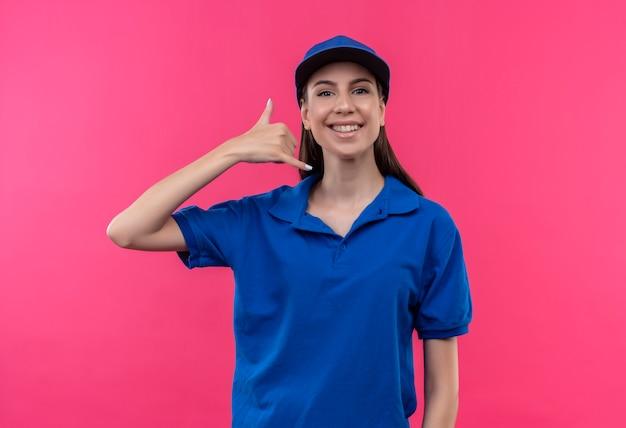 Jovem entregadora de uniforme azul e boné sorrindo alegremente fazendo gesto de me ligar