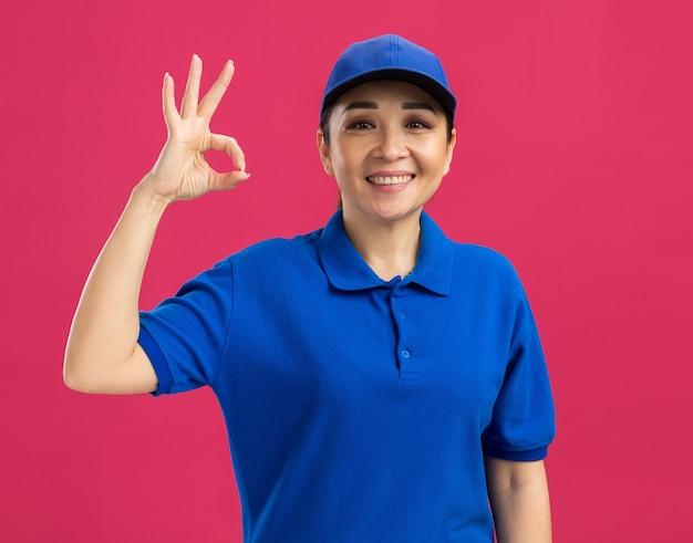 Jovem entregadora de uniforme azul e boné sorrindo alegremente fazendo sinal de ok em pé sobre a parede rosa