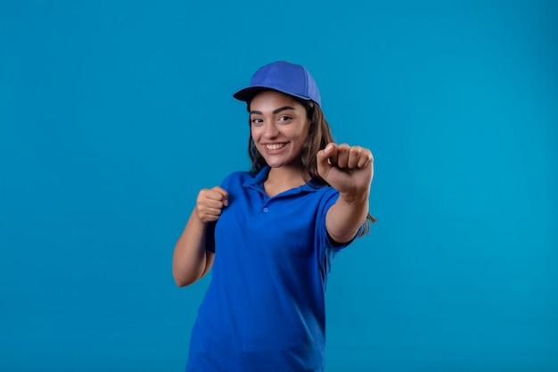 Jovem entregadora de uniforme azul e boné sorrindo alegremente se passando por um boxeador com punhos em pé sobre um fundo azul