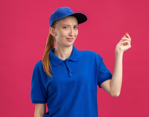 Jovem entregadora de uniforme azul e boné sorrindo, fazendo gesto de dinheiro, esfregando os dedos em pé sobre a parede rosa
