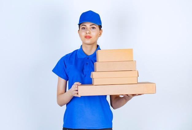 Jovem entregadora de uniforme azul, segurando caixas de papelão em fundo branco.