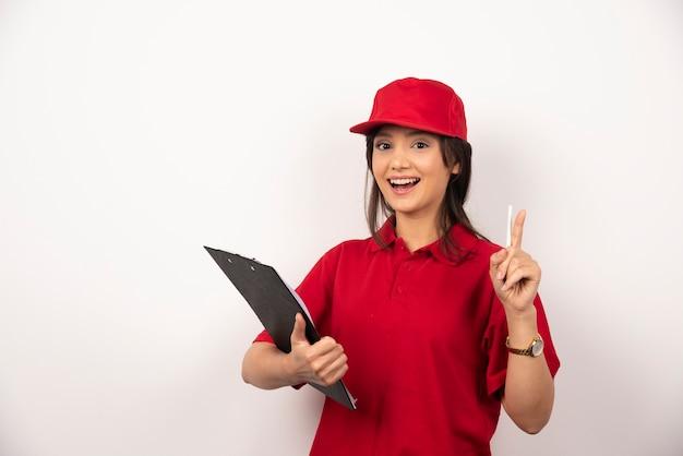 Jovem entregadora de uniforme vermelho com prancheta em fundo branco.