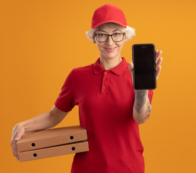Jovem entregadora de uniforme vermelho e boné de óculos, mostrando um smartphone segurando caixas de pizza e sorrindo alegremente em pé sobre uma parede laranja