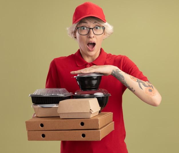 Jovem entregadora de uniforme vermelho e boné de óculos segurando caixas de pizza e pacotes de comida feliz e surpresa em pé sobre a parede verde