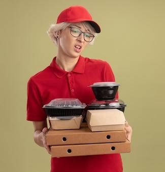 Jovem entregadora de uniforme vermelho e boné de óculos segurando caixas de pizza e pacotes de comida olhando para eles com uma expressão triste em pé sobre a parede verde
