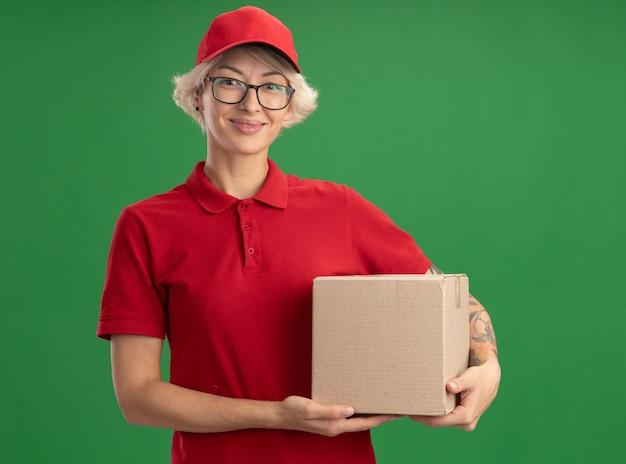 Jovem entregadora de uniforme vermelho e boné de óculos segurando uma caixa de papelão, parecendo sorridente e confiante em pé sobre a parede verde