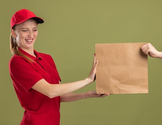 Jovem entregadora de uniforme vermelho e boné se recusando a receber um pacote de papel em pé sobre a parede verde