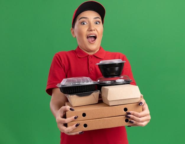 Jovem entregadora de uniforme vermelho e boné segurando caixas de pizza e pacotes de comida olhando para a frente espantada e surpresa em pé sobre a parede verde