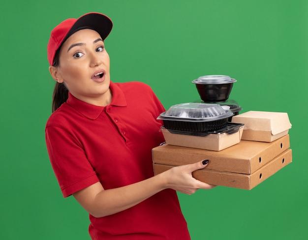 Jovem entregadora de uniforme vermelho e boné segurando caixas de pizza e pacotes de comida olhando para a frente ficando confusa e preocupada em pé sobre a parede verde