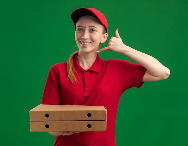 Jovem entregadora de uniforme vermelho e boné segurando caixas de pizza, fazendo gesto de me chamar e sorrindo confiante em pé sobre a parede verde