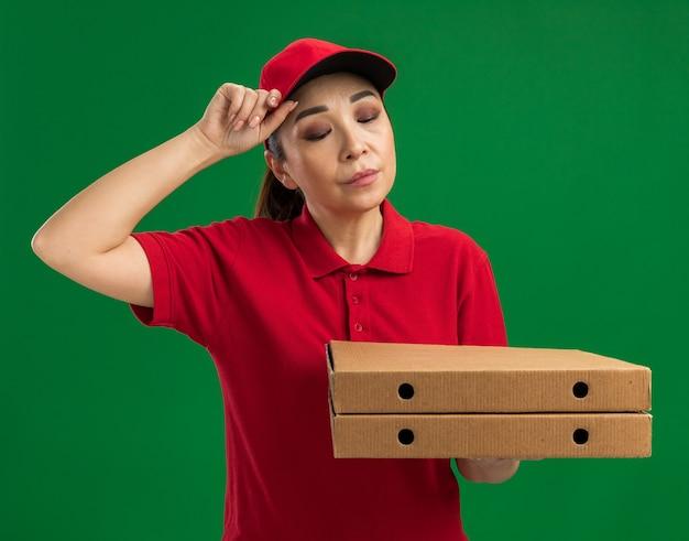 Jovem entregadora de uniforme vermelho e boné segurando caixas de pizza olhando para baixo com uma expressão triste em pé sobre a parede verde
