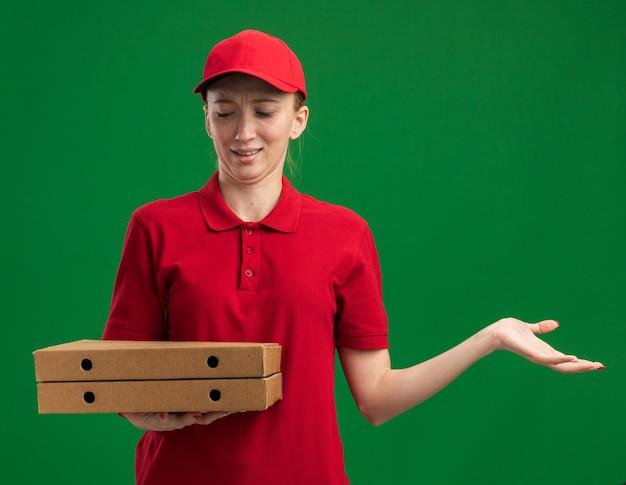 Jovem entregadora de uniforme vermelho e boné segurando caixas de pizza, olhando para elas confusa com o braço estendido em pé sobre a parede verde