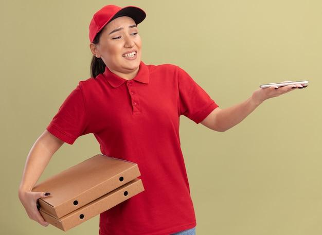 Jovem entregadora de uniforme vermelho e boné segurando caixas de pizza, olhando para o smartphone na mão com uma expressão confusa em pé sobre a parede verde
