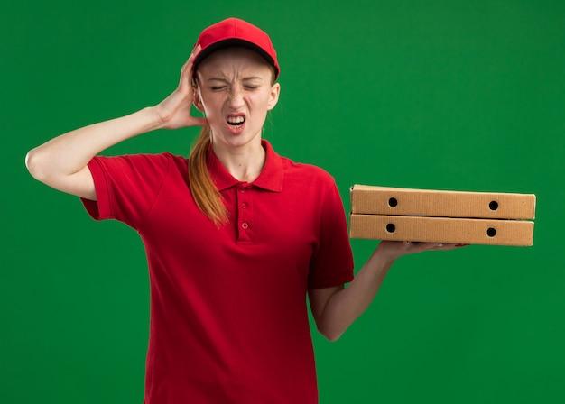 Jovem entregadora de uniforme vermelho e boné segurando caixas de pizza, parecendo confusa com a mão na cabeça por engano em pé sobre a parede verde