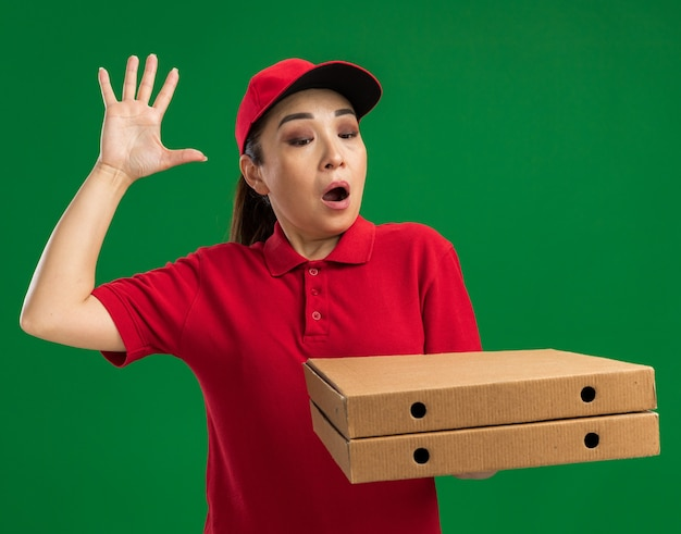 Jovem entregadora de uniforme vermelho e boné segurando caixas de pizza parecendo espantada e surpresa com o braço levantado em pé sobre a parede verde