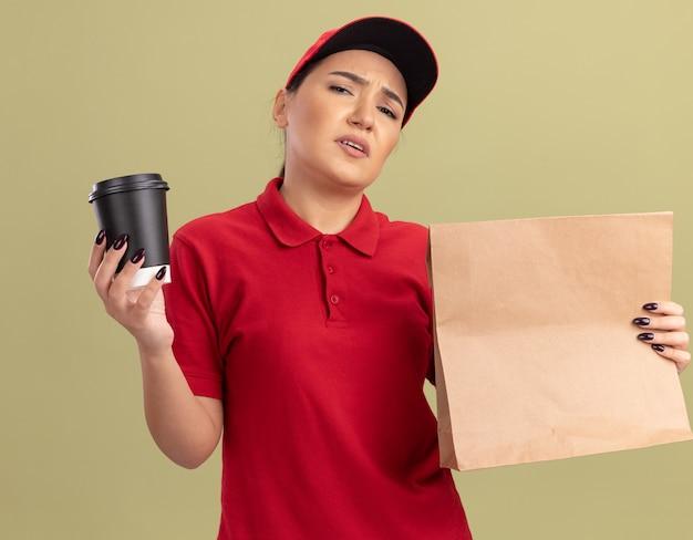 Jovem entregadora de uniforme vermelho e boné segurando um pacote de papel e uma xícara de café, olhando para a frente e ficando descontente em pé sobre a parede verde