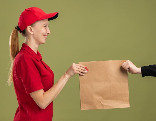 Jovem entregadora de uniforme vermelho e boné segurando um pacote de papel, entregando a um cliente sorrindo confiante sobre a parede verde