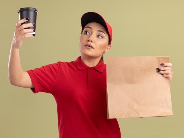 Jovem entregadora de uniforme vermelho e boné segurando um pacote de papel olhando para a xícara de café na outra mão com uma cara séria em pé sobre a parede verde