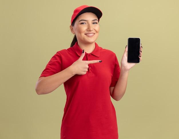 Jovem entregadora de uniforme vermelho e boné segurando um smartphone apontando com o dedo indicador para ele e sorrindo confiante em pé sobre a parede verde
