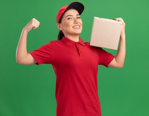 Jovem entregadora de uniforme vermelho e boné segurando uma caixa de papelão olhando para frente sorrindo alegremente, levantando o punho como um vencedor em pé sobre uma parede verde
