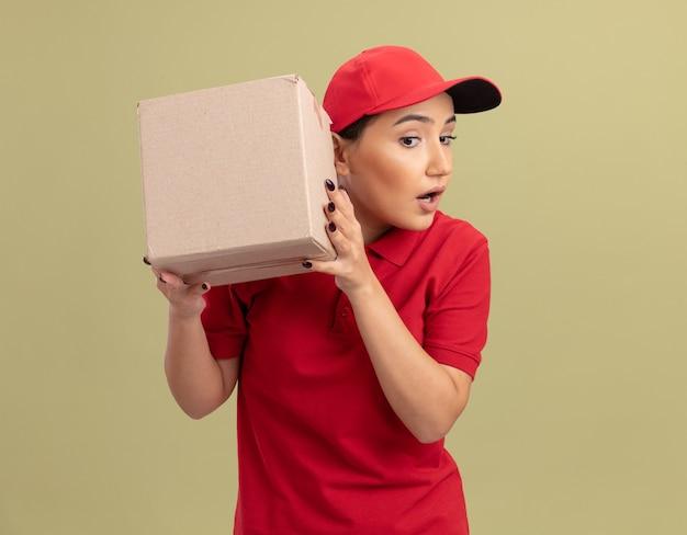 Jovem entregadora de uniforme vermelho e boné segurando uma caixa de papelão sobre a orelha, ouvindo em pé sobre uma parede verde