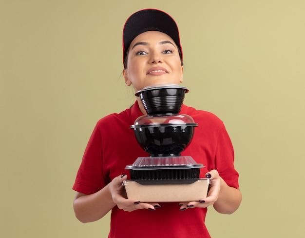 Jovem entregadora de uniforme vermelho e boné segurando uma pilha de pacotes de comida olhando para a frente sorrindo alegremente em pé sobre a parede verde
