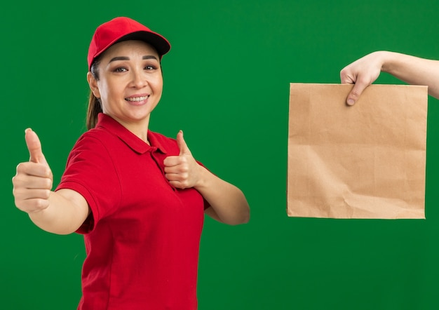 Jovem entregadora de uniforme vermelho e boné sorrindo, mostrando os polegares para cima enquanto recebe um pacote de papel em pé sobre a parede verde