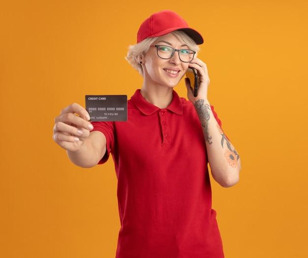 Jovem entregadora de uniforme vermelho e boné usando óculos, falando no celular, mostrando o cartão de crédito, sorrindo confiante em pé sobre a parede laranja