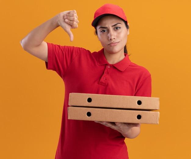 Jovem entregadora descontente de uniforme e boné segurando caixas de pizza com o polegar isolado na parede laranja