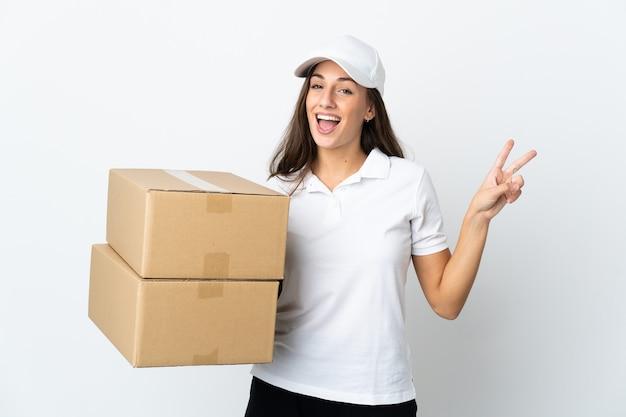 Jovem entregadora em branco isolado sorrindo e mostrando sinal de vitória