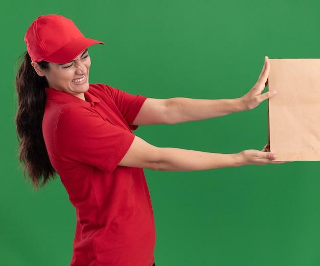 Jovem entregadora enjoada de uniforme e boné, dando um pacote de comida de papel para um cliente isolado na parede verde