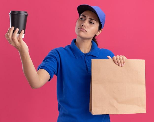 Jovem entregadora impressionada, vestindo uniforme com boné segurando um pacote de comida de papel e olhando para a xícara de café na mão isolada na parede rosa