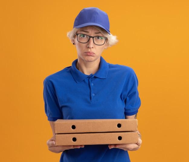 Jovem entregadora insatisfeita de uniforme azul e boné de óculos, segurando caixas de pizza, com expressão triste na parede laranja