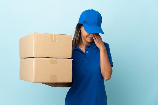 Jovem entregadora isolada na parede azul com expressão cansada e doente