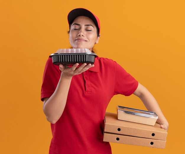 Jovem entregadora satisfeita de uniforme e boné, segurando caixas de pizza e cheirando recipientes de comida na mão, isolada na parede laranja