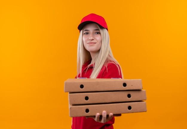 Jovem entregadora satisfeita vestindo camiseta vermelha e boné segurando uma caixa de pizza em um fundo laranja isolado