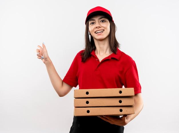 Jovem entregadora satisfeita vestindo uniforme vermelho e boné segurando uma pilha de caixas de pizza apontando com o dedo indicador para o lado sorrindo alegremente em pé sobre um fundo branco