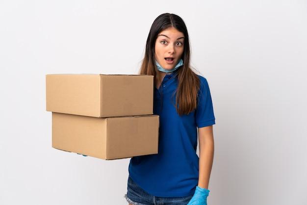 Jovem entregadora se protegendo do coronavírus com uma máscara isolada no branco com expressão facial surpresa e chocada