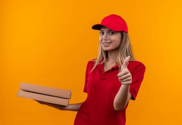 Jovem entregadora sorridente com uniforme vermelho e boné segurando uma caixa de pizza com o polegar isolado na parede laranja