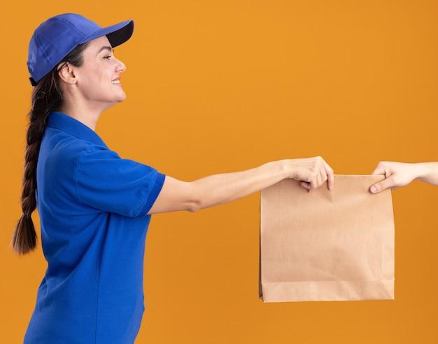 Jovem entregadora sorridente de uniforme e boné em vista de perfil, dando um pacote de papel para o cliente, olhando para o cliente