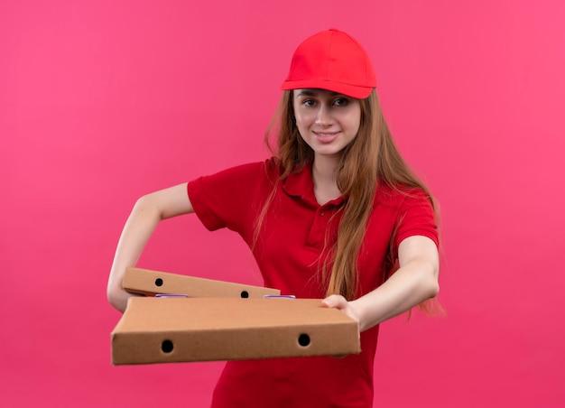 Jovem entregadora sorridente de uniforme vermelho segurando e esticando pacotes em um espaço rosa isolado