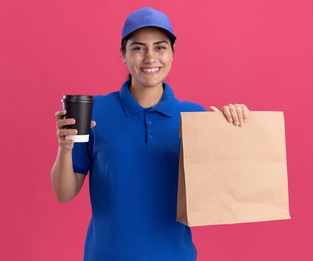 Jovem entregadora sorridente, usando uniforme com tampa, segurando um pacote de comida de papel com uma xícara de café isolada na parede rosa