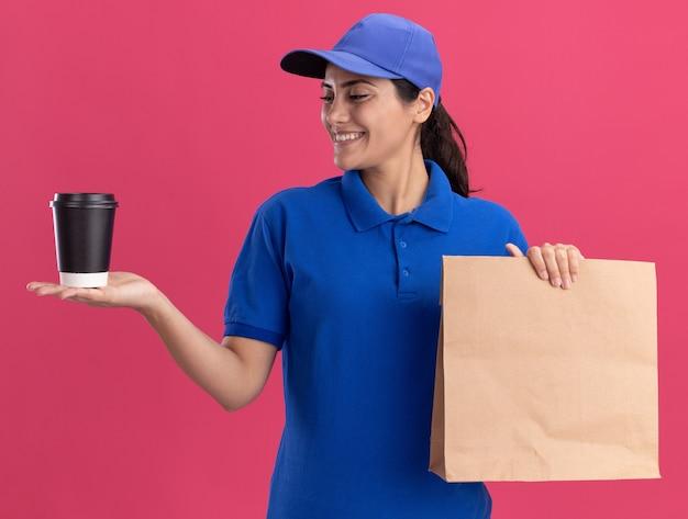 Jovem entregadora sorridente, usando uniforme com tampa, segurando um pacote de comida de papel e olhando para a xícara de café na mão, isolada na parede rosa