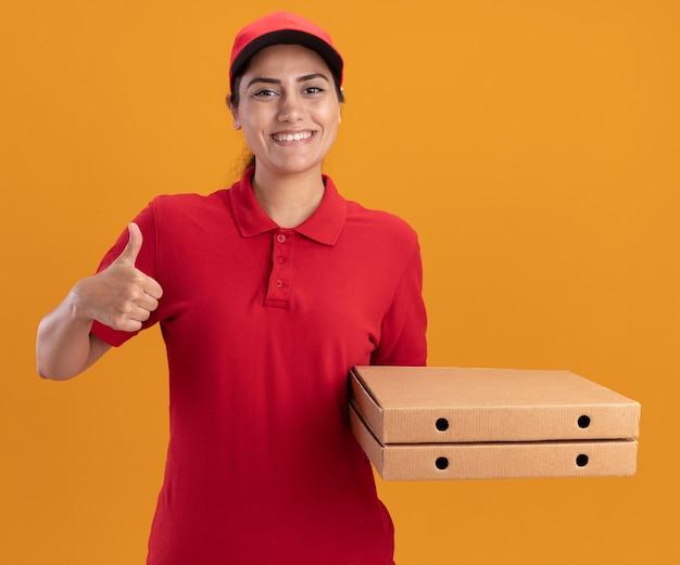 Jovem entregadora sorridente usando uniforme e boné segurando caixas de pizza aparecendo o polegar isolado na parede laranja