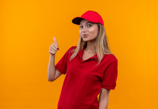 Jovem entregadora sorridente, usando uniforme vermelho e boné com o polegar isolado na parede laranja