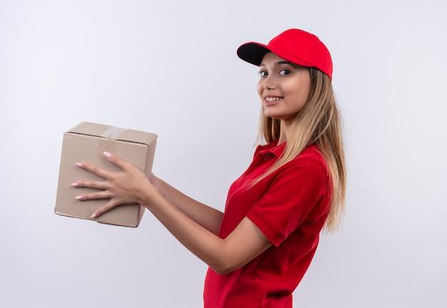 Jovem entregadora sorridente usando uniforme vermelho e boné segurando uma caixa ao lado, isolada na parede branca