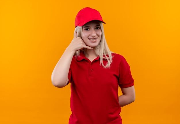 Jovem entregadora sorridente, vestindo camiseta vermelha e boné no aparelho dentário, mostrando gesto de chamada em fundo laranja isolado