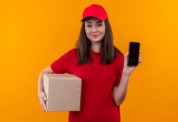 Jovem entregadora sorridente, vestindo uma camiseta vermelha com boné vermelho, segurando uma caixa e um telefone na parede laranja isolada
