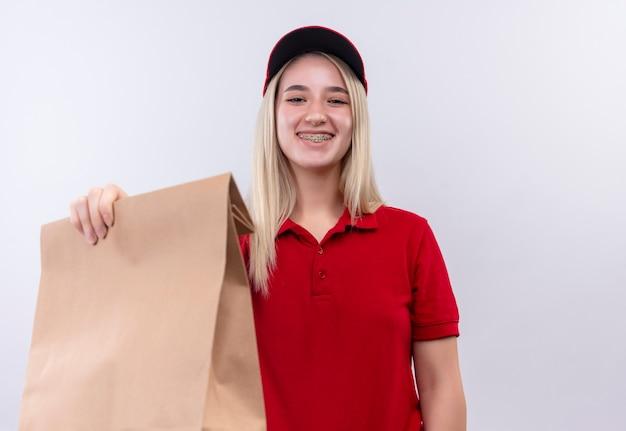 Jovem entregadora sorridente, vestindo uma camiseta vermelha e boné com aparelho dentário segurando no bolso de papel da câmera no fundo branco isolado