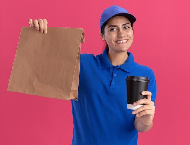 Jovem entregadora sorridente, vestindo uniforme com tampa, segurando um pacote de comida de papel com uma xícara de café isolada na parede rosa